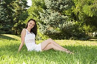 Cute young female sitting on grass field at the park