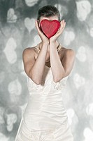 a woman in a wedding dress holding a heart in front of the face