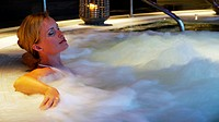 Woman bathing in jacuzzi of spa center
