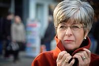 Portrait einer grauhaarigen Dame mit rotem Mantel