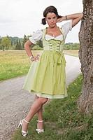 Junge Frau mit Dirndl lehnt sich an einen Baumstamm