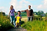 Familie zu Fuß und mit Fahrrad im Sommer