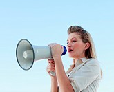 Blonde businesswoman shouting through megaphone