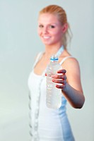 Happy woman holding a bottle of water with focus on water