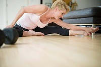 Caucasian woman stretching on floor
