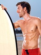 Young muscular man with a surfboard at the beach enjoying summer