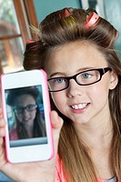 Little girl with hair curlers photographing herself with cell phone