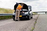 Stranded motorist attempting to fix his broken down car on the shoulder of a motorway