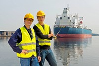 Two dockers posing in front of a large oil tanker in an industrial harbor