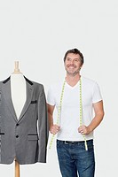Mature male dressmaker standing next to tailor´s dummy over gray background