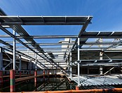Structural steel construction of an office building. Framework of beams creating a ceiling and walls. Looking upwards to the sky