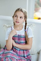 Young girl thinking while sitting on sofa