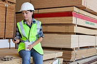 Female industrial worker taking break from work at timber yard