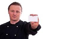 Ein Koch hält mit einer Hand eine Blanko_Vistienkarte nach vorne