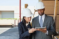Multiethnic contractors using tablet PC at timber yard