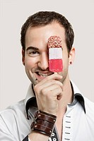 Close_up portrait of young man holding ice cream bar against gray background