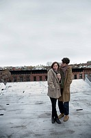 A young couple standing on a roof in winter