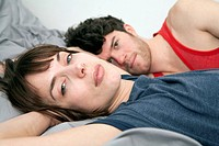 A young couple lying in bed together, close_up