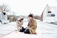 A young couple ignoring each other while sitting on a roof in winter (thumbnail)