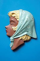 A retro wall hanging of a woman with blond hair and a headscarf