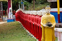 A row of Buddhist monk statues in a procession behind a Buddha statue, Hpa_An, Burma