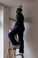 A man standing on a ladder and painting a wall