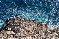 wild blue sea hitting rocky coast and foaming