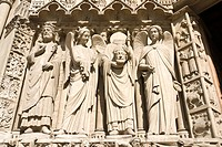 Statues on the left side of the left portal Portail de la Vierge of Notre_Dame cathedral, representing a not identified king, an angel, Saint Denis ca...