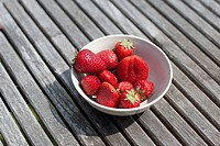 A bowl of strawberries on an outdoor table