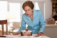 A senior woman blowing out a candle on a cake