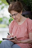 A senior woman writing in a book