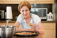 A senior woman with freshly baked cookies