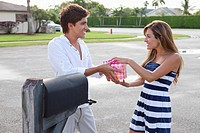 A young couple standing by mailbox, playfully fighting over a gift