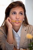 A businesswoman biting a pencil and looking up in contemplation