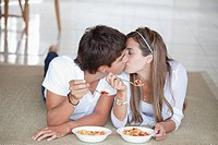 A young couple kissing while eating breakfast