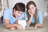 A young cheerful couple counting coins on the floor