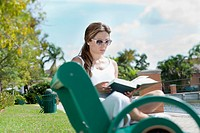 A woman reading a book on a park bench