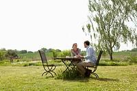 A couple having breakfast in their backyard
