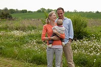 A man and a woman holding a baby standing in their backyard (thumbnail)