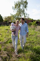 A man and a woman holding a baby walking in back of their country house