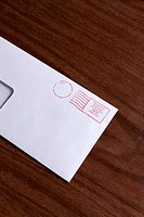 A window envelope with a red ink postage stamp