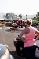 A woman looking at the scene of a burning house in a suburb