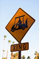 A sign for golf carts crossing