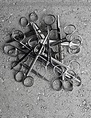 A pile of surgical scissors on cement
