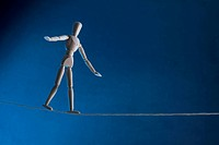 An artist's figure walking a tightrope