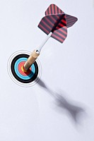 A dart stuck in the bull's eye of a miniature archery target