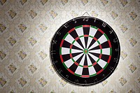 A dartboard hanging on a wallpapered wall