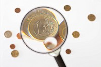 A magnifying glass magnifying a one Euro coin