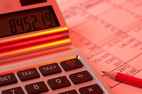 A calculator on a financial document illuminated in red light