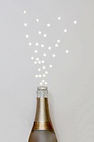 Star shaped confetti spraying out of a champagne bottle